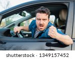 Small photo of Angry and rude man driving road rage