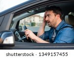 Small photo of Man driving car despair after car accident