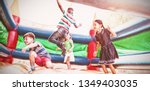 Small photo of Friends jumping on bouncy castle at playground