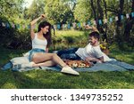 young couple on a picnic in a... | Shutterstock . vector #1349735252