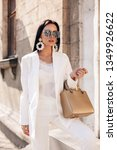 Small photo of fashion interior photo of beautiful woman with dark hair in elegant white suit and coat, with accessories posing on the spring street