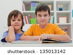 two happy boys reading a book... | Shutterstock . vector #135013142