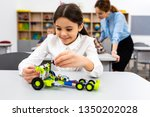 smiling schoolgirl playing with ... | Shutterstock . vector #1350202028