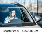young and happy woman driving a ... | Shutterstock . vector #1350383225