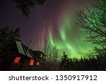 The Aurora Borealis dancing over a cabin, Whitehorse, Yukon, Canada