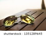 sunglass on wood table and... | Shutterstock . vector #1351289645
