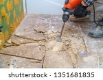 Small photo of Worker remove, demolish old tiles a bathroom with jackhammer