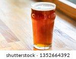 pint of draft beer on a wooden... | Shutterstock . vector #1352664392