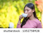 the girl is sipping coffee with ... | Shutterstock . vector #1352758928