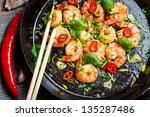Shrimps sauteed with chilli pepper on old black pan - stock photo