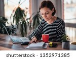 woman sitting at the table by... | Shutterstock . vector #1352971385