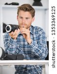 young man checking lens of his camera