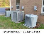 Small photo of 3 Air Conditioner Compressors outside commercial building with cutoff switches.