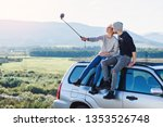 Young hipster couple in love making selfie using smart phone while sitting on the roof of off-road car on mountain background. Traveling, activism and friendship concept. - stock photo