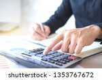 Small photo of Men use the calculator and take notes with calculations about the expenses at the office. Prepare to submit annual tax