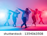 Small photo of Young modern dancing group of six adult young people practice dancing on colorful background. Fashionably dressed youngsters moving over blurred disco club color lights