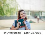 the girl blinks with one eye... | Shutterstock . vector #1354287098