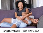 laughing mixed race mother... | Shutterstock . vector #1354297565