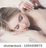 young woman lying on a massage...   Shutterstock . vector #1354358975