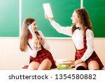 two beautiful schoolgirls are... | Shutterstock . vector #1354580882