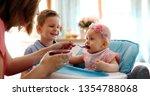 mother feeding her baby girl... | Shutterstock . vector #1354788068