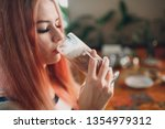 young girl drinks hot chocolate ... | Shutterstock . vector #1354979312