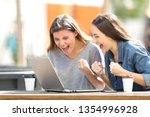 Two excited women checking laptop online content sitting in a park