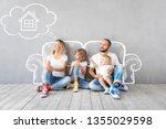 Small photo of Happy family with two kids playing into new home. Father, mother and children having fun together. Moving house day and real estate concept