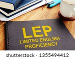 Small photo of Limited English Proficiency LEP documents on a desk.