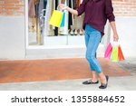 consumerism woman holding many... | Shutterstock . vector #1355884652