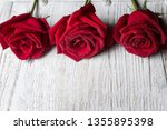 Three Red Roses On Light Woode...
