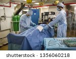 Small photo of San Diego, California, USA – July 31, 2017: Horizontal shot of a two fake doctors and a nurse operating on a patient in the sick bay and hospital of the USS Midway aircraft carrier, Navy Pier