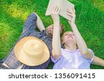 man and girl lay on grass... | Shutterstock . vector #1356091415
