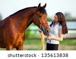 Stock photo child riding a horse in meadow in spring 135613838