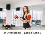 beautiful girl in the gym.... | Shutterstock . vector #1356542558