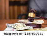 Small photo of Corrupt court.Trial of money scammers. Judge's gavel and bundles of money on the judge's table.