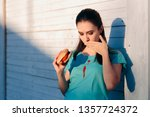 Small photo of Clumsy Woman Staining Her Shirt with Ketchup Sauce. Lady ruining her t-shirt with tomato sauce eating burger