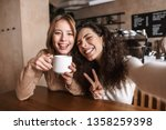Stock photo image of excited happy pretty girls friends sitting in cafe take a selfie by camera 1358259398