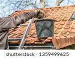 man on a ladder cleaning house... | Shutterstock . vector #1359499625