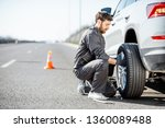 Handsome road assistance worker in uniform changing car wheel on the highway - stock photo