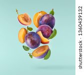Stock photo flying in air fresh ripe whole and cut plums with leavs isolated on pastel turquoise background 1360439132