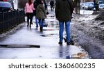 Small photo of A young man stands on the road while everyone else goes on. Melting snow and puddles that people go with bags about their business. Parking cars on the background and growing trees. Dirty street.