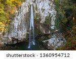 waterfall falls from a cliff.... | Shutterstock . vector #1360954712