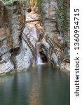 waterfall falls from a cliff.... | Shutterstock . vector #1360954715