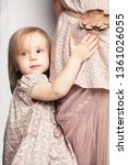 Stock photo baby girl holding her mother skirt childhood concept 1361026055