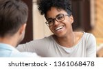 Small photo of Happy young interracial couple pretty african american woman and caucasian man boyfriend laugh flirt enjoy fun conversation on first date, mixed race teen girl in love talking having fun at meeting