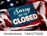 Small photo of Government shutdown, Washington is broken, political deadlock and partisan politics concept theme with a sorry we're closed sign and the American flag