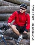 mountain biker resting on wood...   Shutterstock . vector #136141622