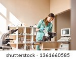 Stock photo everything will be fine young female vet bandaging a paw of a big black cat lying on the table in 1361660585