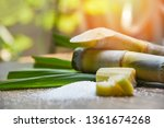 Small photo of White sugar and sugar cane on wooden table and nature background